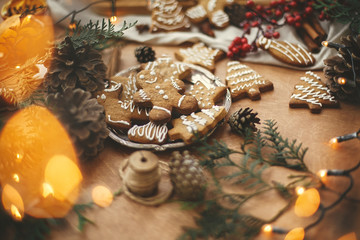 Merry Christmas. Festive gingerbread cookies with anise, cinnamon, pine cones, cedar branches and golden lights bokeh on rustic table. Atmospheric image. Seasons greetings