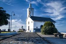 Iglesia De Paredes Blancas Al Final De Un Camino Empedrado Con Un Faro Al Fondo