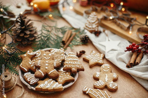 Obraz na plátně Christmas gingerbread cookies on vintage plate and anise, cinnamon, pine cones, cedar branches  with golden lights on rustic table