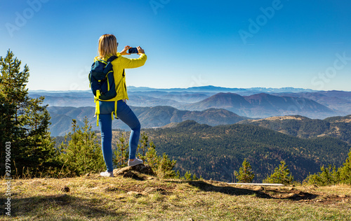 Fototapeta Female hiker with backpack standing on top of the mountain photographing and enjoying the view during the day. obraz