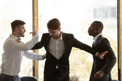 Obraz na plátně  Male colleague set apart angry diverse businessmen fighting in office