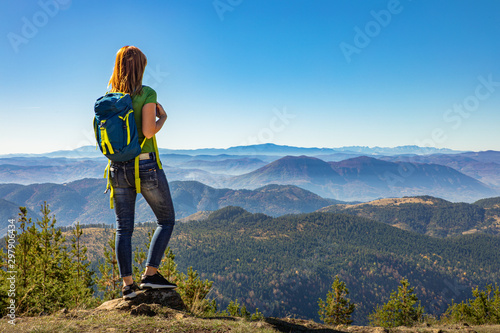 Fototapeta Rear view of female hiker with backpack standing on top of the mountain and enjoying the view during the day. obraz