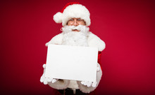 An Invitation. Authentic Santa Claus Is Posing On A Red Background, Holding A Blank Postcard And Showing It At The Camera.