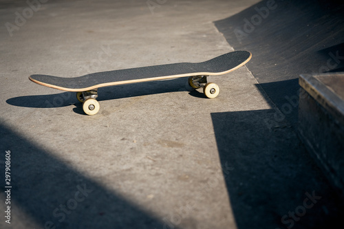 Fotomural View of black skateboard in concrete skatepark on warm day