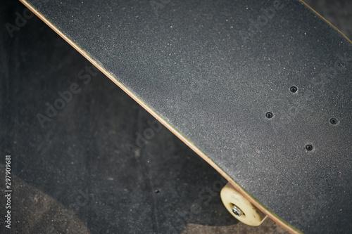 Fotomural  Top view of skateboard in concrete skatepark on warm day