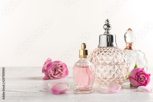 Fototapeta Different bottles of perfume and flowers on light background, space for text obraz