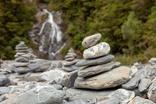 Pile Of Rocks That Mark The Way For Hikers Along A River.