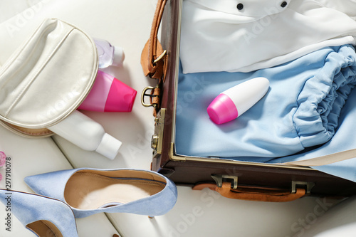 Vintage suitcase with deodorants and clothes indoors, closeup view Wallpaper Mural