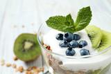 Tasty homemade granola dessert on white wooden table, closeup. Healthy breakfast