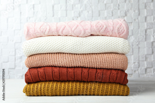 Fotografía  Stack of warm clothes on white wooden table against textured wall