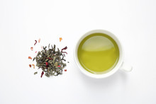 Green Tea Leaves And Cup Of Hot Beverage On White Background, Flat Lay