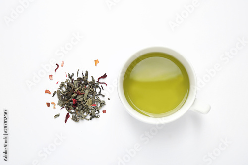 Green tea leaves and cup of hot beverage on white background, flat lay Wallpaper Mural