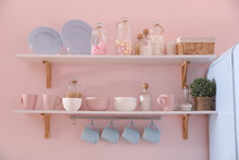 Shelves With Dishware And Products On Pink Wall In Kitchen