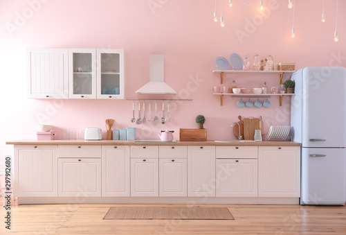 Photo Stylish pink kitchen interior with modern furniture and fridge