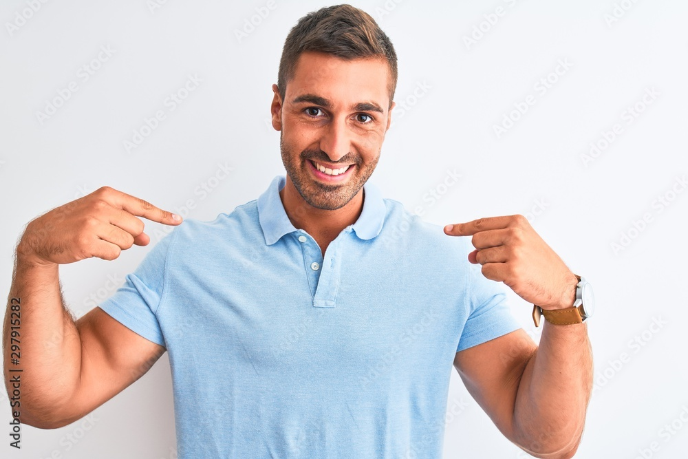 Fototapeta Young handsome elegant man wearing blue t-shirt over isolated background looking confident with smile on face, pointing oneself with fingers proud and happy.