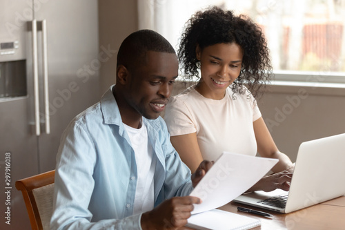Fototapeta Happy african american family couple planning family budget, monthly expenses. obraz