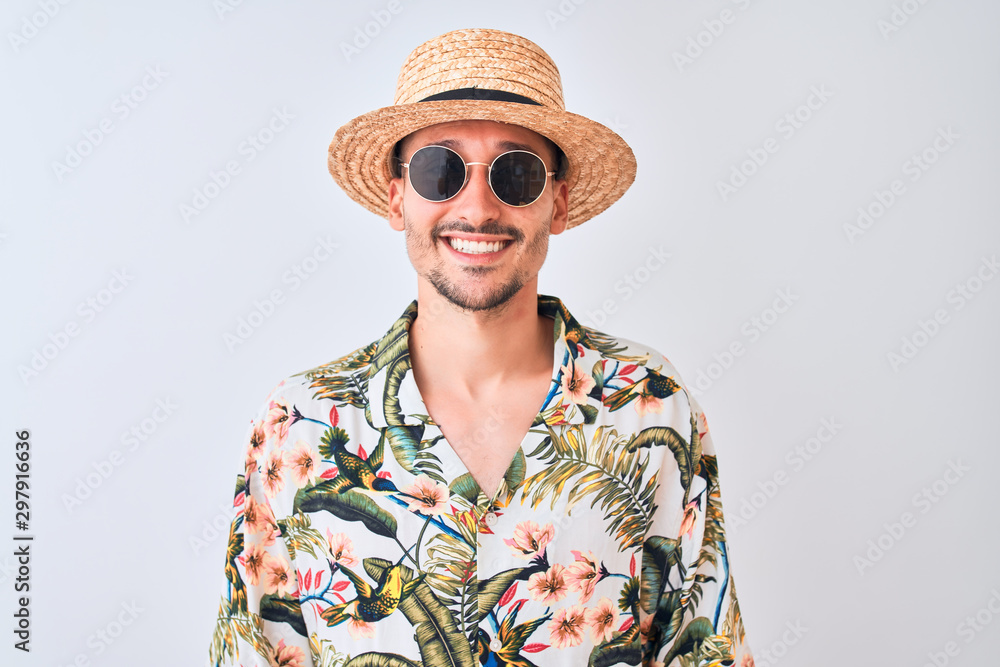 Fototapeta Young handsome man wearing Hawaiian shirt and summer hat over isolated background with a happy and cool smile on face. Lucky person.