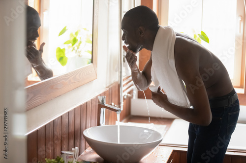 Fotografía  Smiling african american guy bending over sink with running water