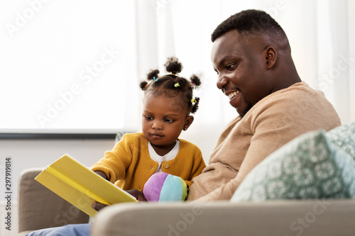 Foto op Canvas Wild West family, fatherhood and people concept - happy african american father reading book for baby daughter at home