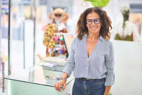 Fotografía  Middle age beautiful clothes shop owner woman smiling happy and confident waitin