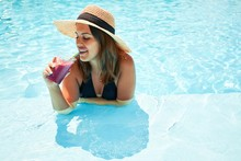 Young Beautiful And Sexy Woman At Swimming At Resort Pool On Vacation, Sunbathing Inside Water On Sunny Day Drinking Slush