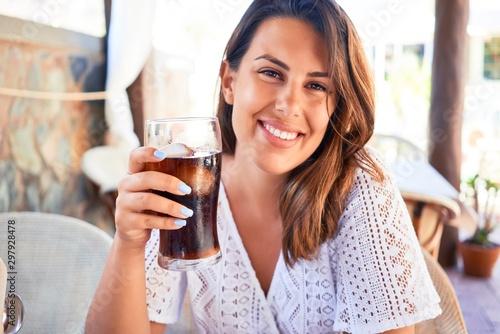 Cuadros en Lienzo Young beautiful woman sitting at restaurant enjoying summer vacation drinking so