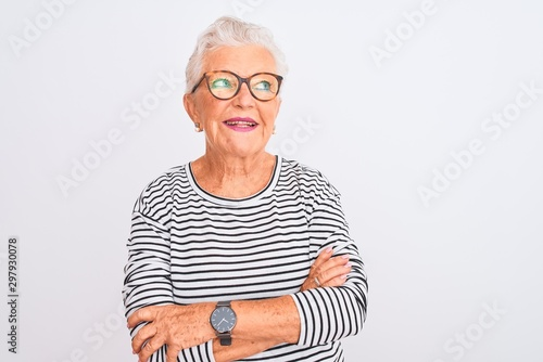 Fotografía  Senior grey-haired woman wearing striped navy t-shirt glasses over isolated white background smiling looking to the side and staring away thinking