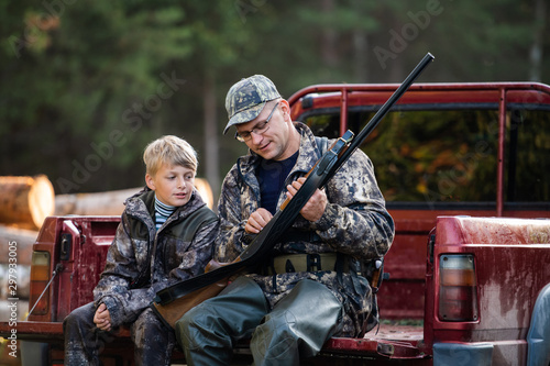 Leinwand Poster Father and son sitting in a pickup truck after hunting in forest