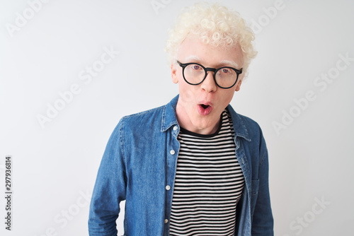 Young albino blond man wearing denim shirt and glasses over isolated white background afraid and shocked with surprise and amazed expression, fear and excited face Canvas Print