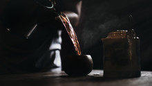 Dark Vintage Background Of Blurred Man Pouring Hot Yellow Chinese Tea To Teacup With Old Traditional Chinese Tea Pot On Table