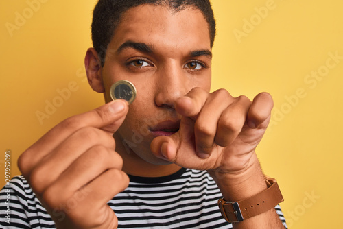 Fotomural  Young handsome arab man holding euro coin standing over isolated yellow backgrou