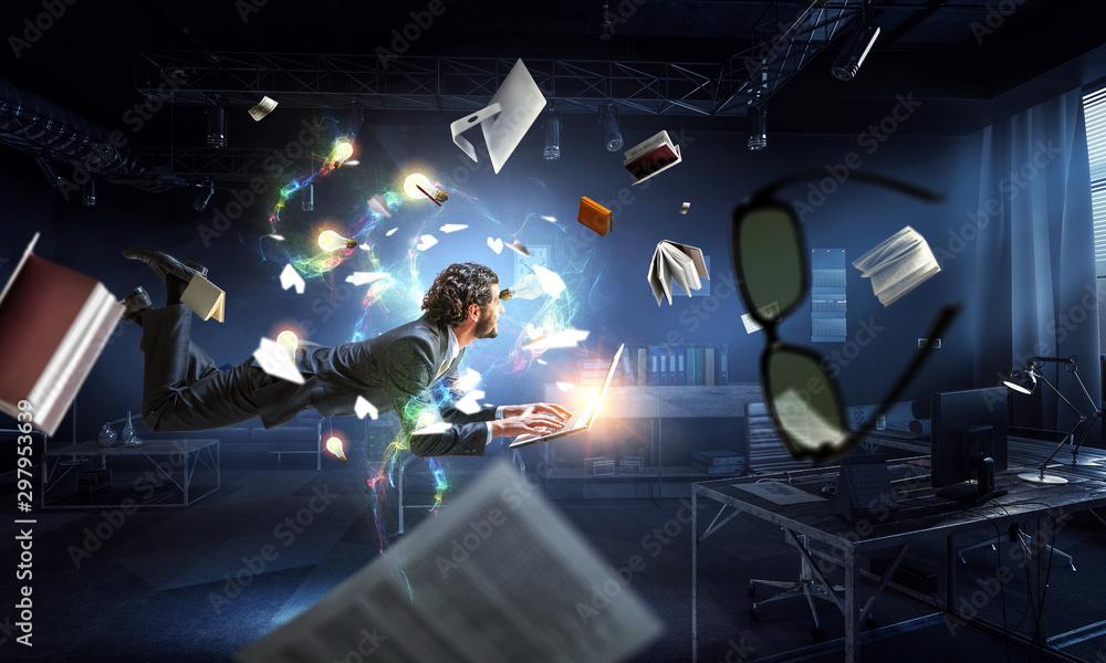 Fototapeta Man flies and works on laptop. Mixed media