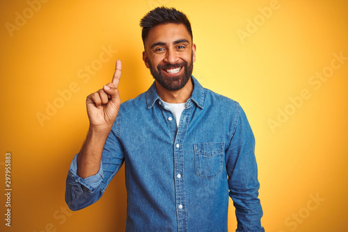 Foto Young indian man wearing denim shirt standing over isolated yellow background showing and pointing up with finger number one while smiling confident and happy