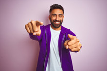 Young Indian Man Wearing Purple Sweatshirt Standing Over Isolated Pink Background Pointing To You And The Camera With Fingers, Smiling Positive And Cheerful