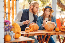 Halloween Preparaton Concept. Young Couple Sitting At Table Outdoors Making Jack-o'-lantern Drawing Face On Pumpkin Concentrated