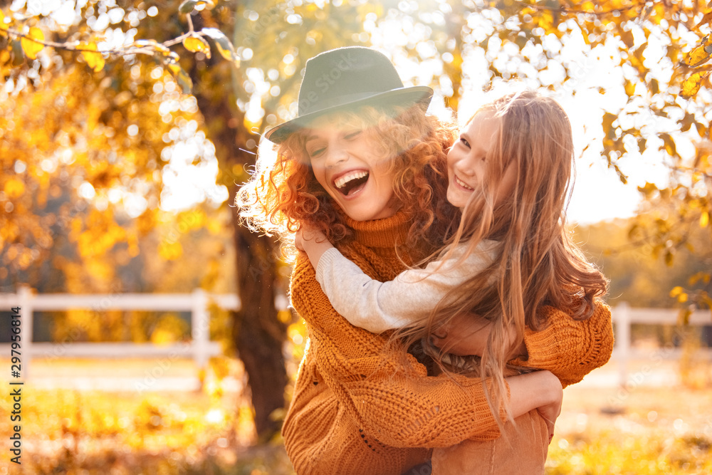 Fototapety, obrazy: Young adult mother hugging her child girl outdoor