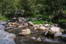 Ancient Bridge Over A Mountain Creek. Mountain River In The Forest On Green Trees Background. Forest Landscape With Water Movement Between Large Stones. Long Exposure.