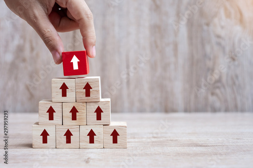 Pinturas sobre lienzo  Businessman hand placing or pulling Red arrow wooden block on table background