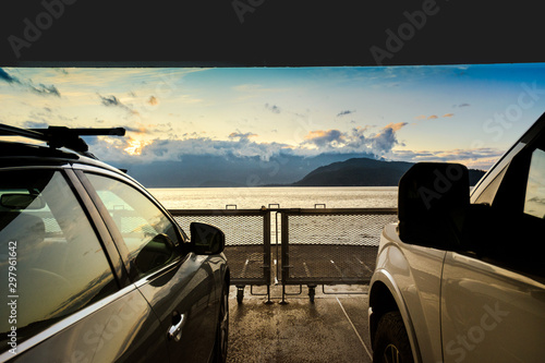 Photo Sunrise over ocean and mountains of Howe Sound, BC, Canada from between parked c