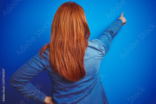 Young beautiful redhead woman wearing denim shirt standing over blue isolated ba Tablou Canvas