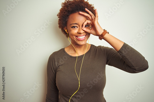 Foto  African american woman wearing earphones listening to music over isolated background doing ok gesture with hand smiling, eye looking through fingers with happy face