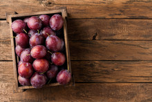 Tasty Plums In Box On Rustic W...
