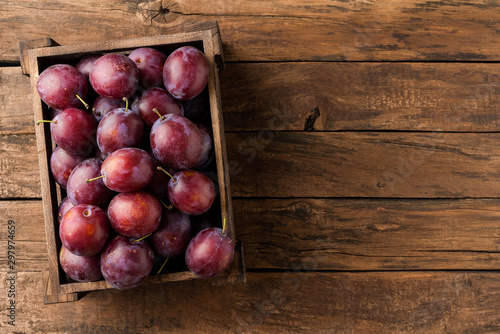 Tasty plums in box on rustic wooden background with copyspace. Top view