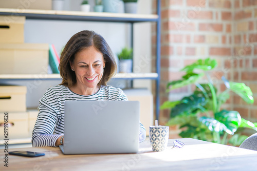 Middle age senior woman sitting at the table at home working using computer lapt Tapéta, Fotótapéta