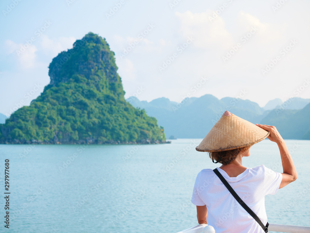 Fototapety, obrazy: Woman with traditional looking at unique view of Halong Bay, Vietnam. Tourist traveling on cruise among Ha Long Bay rock pinnacles in the sea. Caucasian lady having fun on vacation to famous landmark.