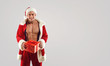 Muscular man in Santa suit holding present