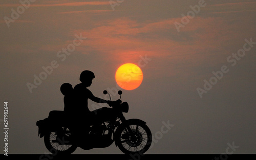 silhouette fatherand son ride classic motorcycle on sunset