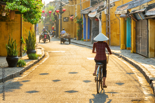 Tuinposter Fiets Vietnamese woman in traditional hat bicycling along Hoi An