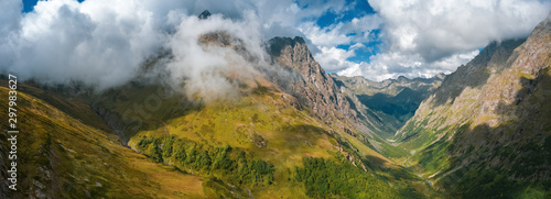 Poster Taupe Panoramic view of river valley with steep stony slopes of mountain ranges; rocky peaks and clouds; climbing and trekking routes for tourists; drone flying between ridges; autumn sunny day, Caucasus