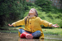 Happy Child Girl With  Rubber Boots In Puddle